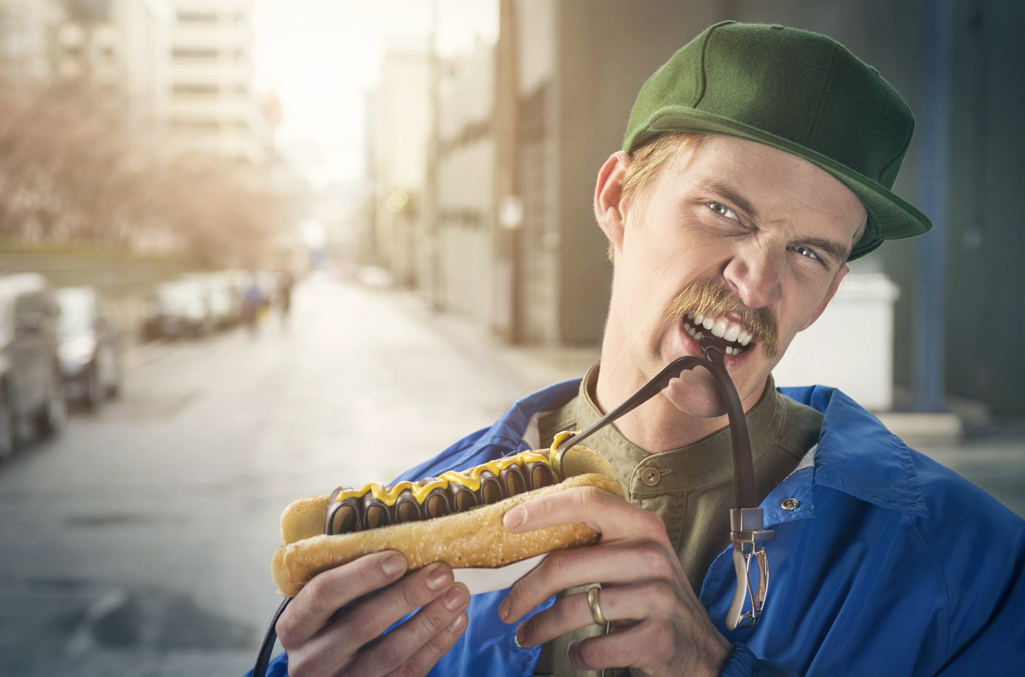 man eating a hotdog where the sausage is a brown leather belt